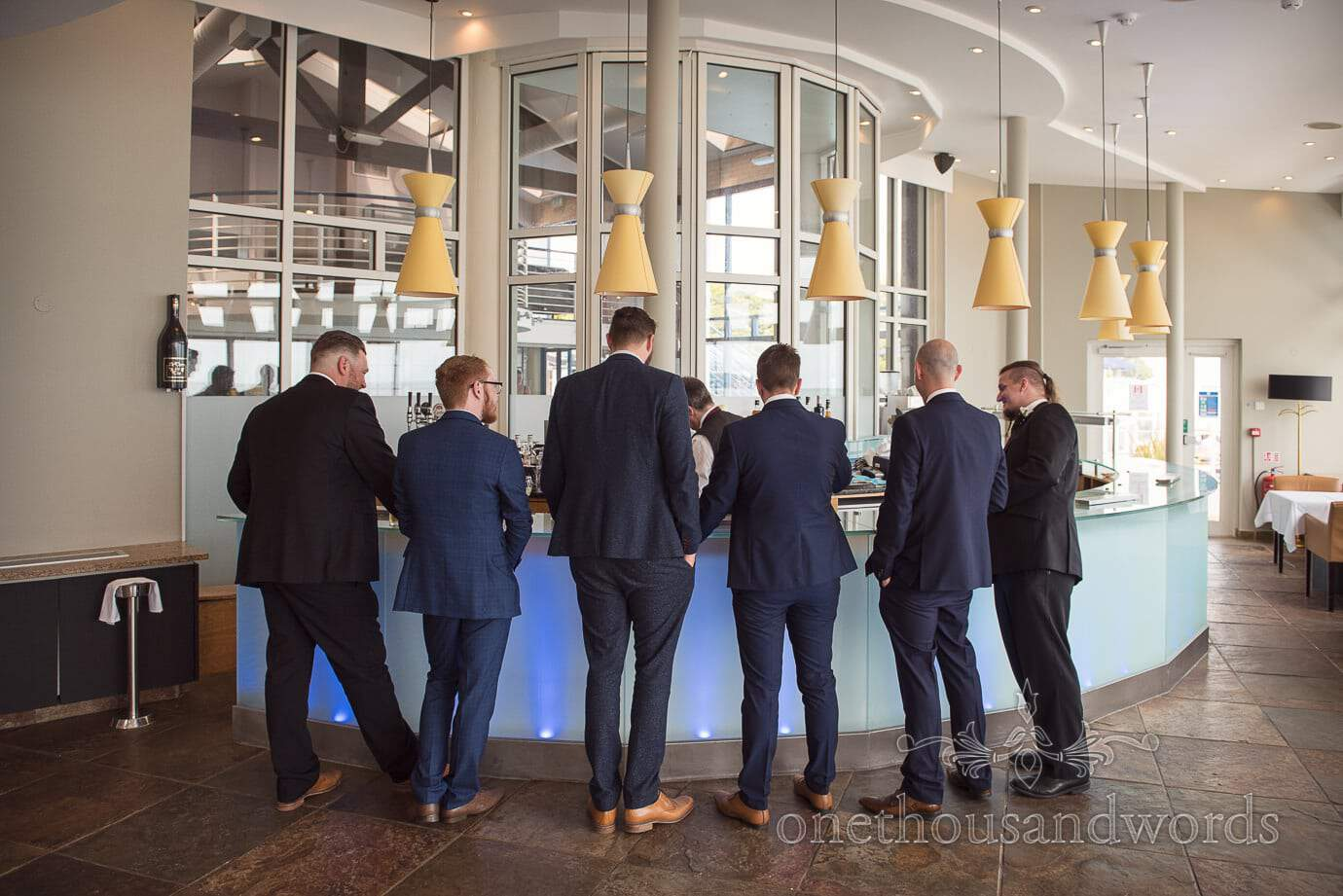 Wedding guests in black and blue suits at designer bar in Haven Hotel wedding venue