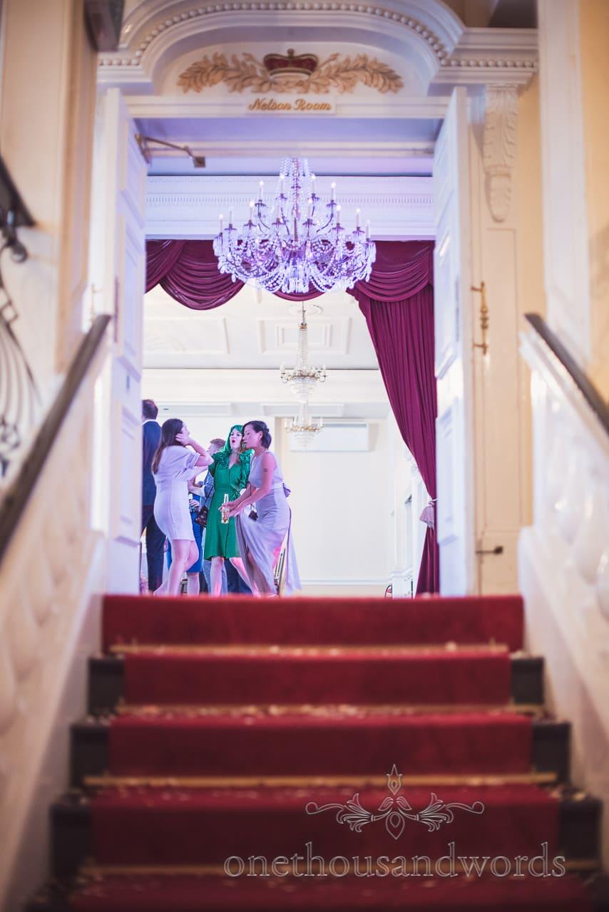Wedding guests in fancy dress dance under chandelier at Greenwich Wedding venue