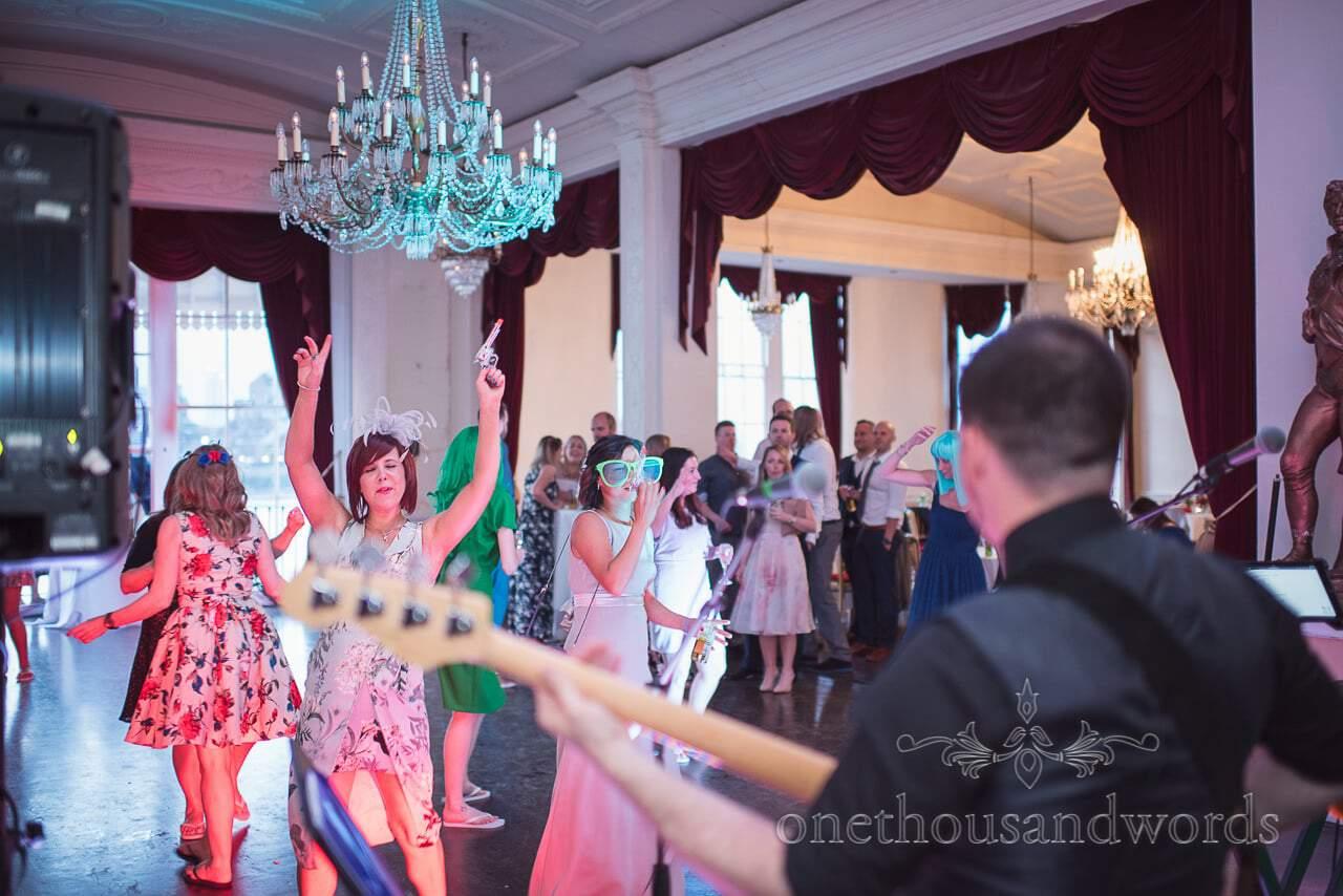 Wedding guests in fancy dress dance under chandelier at Trafalgar Tavern Wedding venue