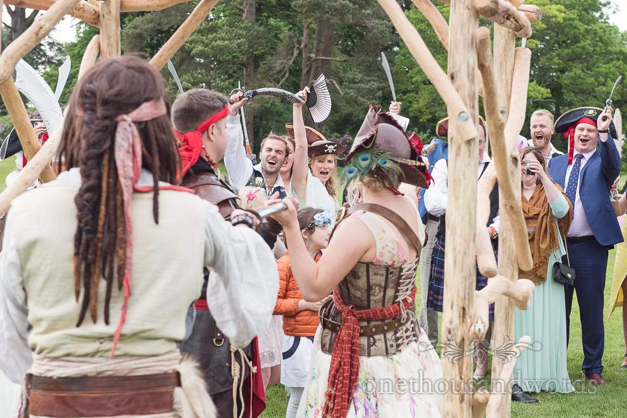Wedding guests in pirate fancy dress celebrate at pirate themed wedding ceremony