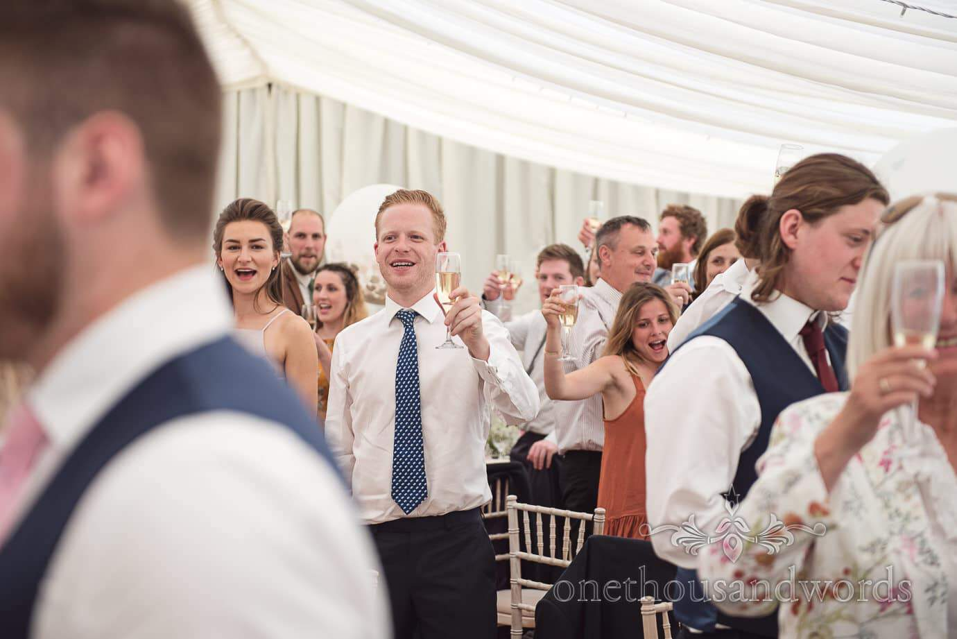 Wedding guests in white marquee raise a toast to the wedding speeches