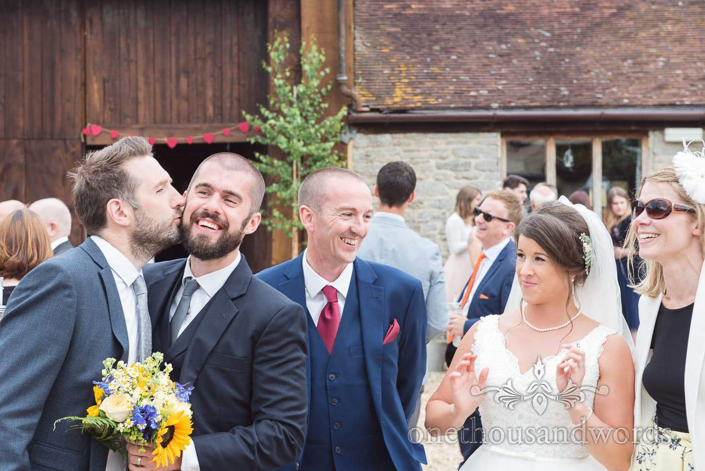 Wedding guests kissing each others beards at Stockbridge farm barn wedding