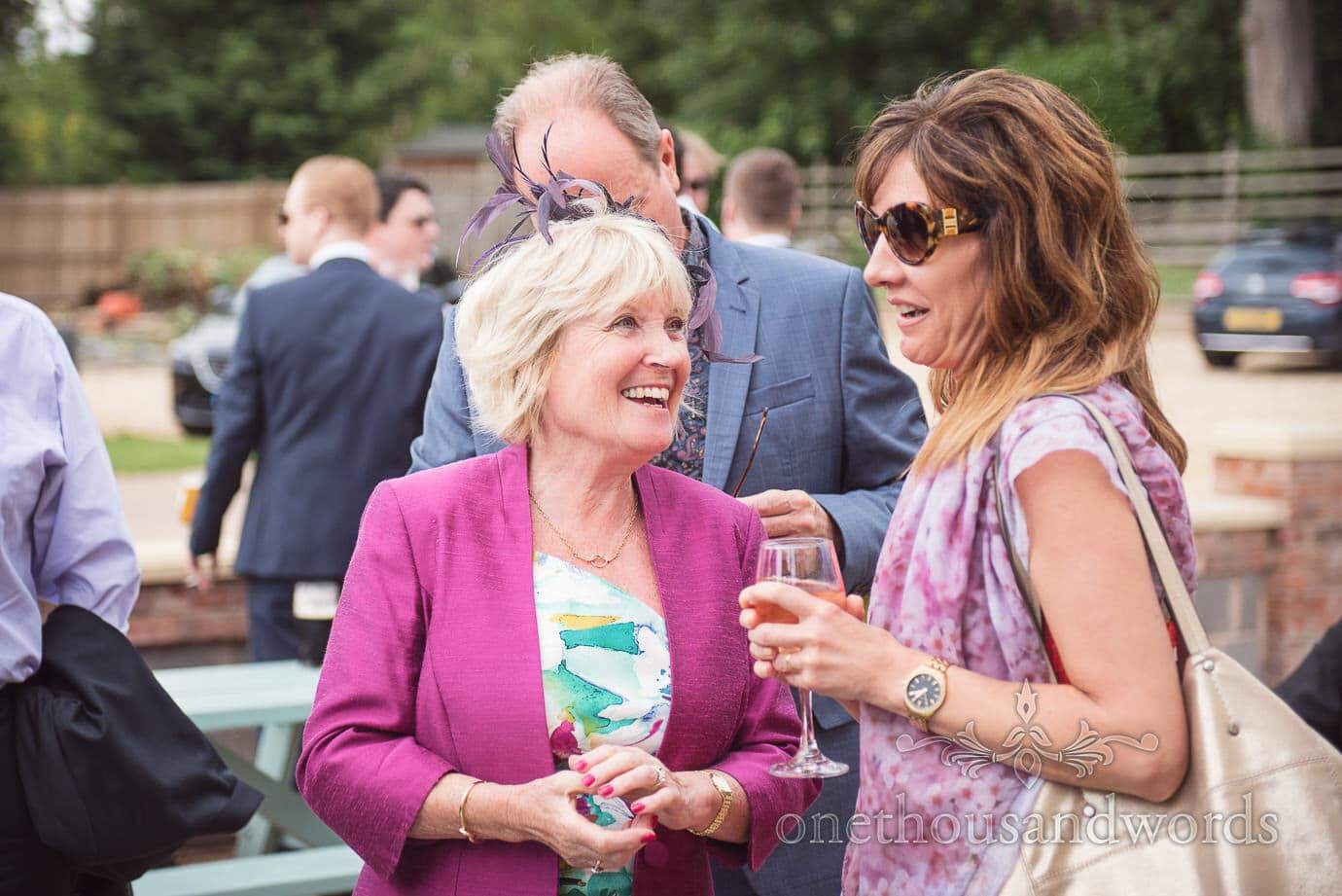 Wedding guests laughing as they enjoy pub drinks in the sun on wedding morning