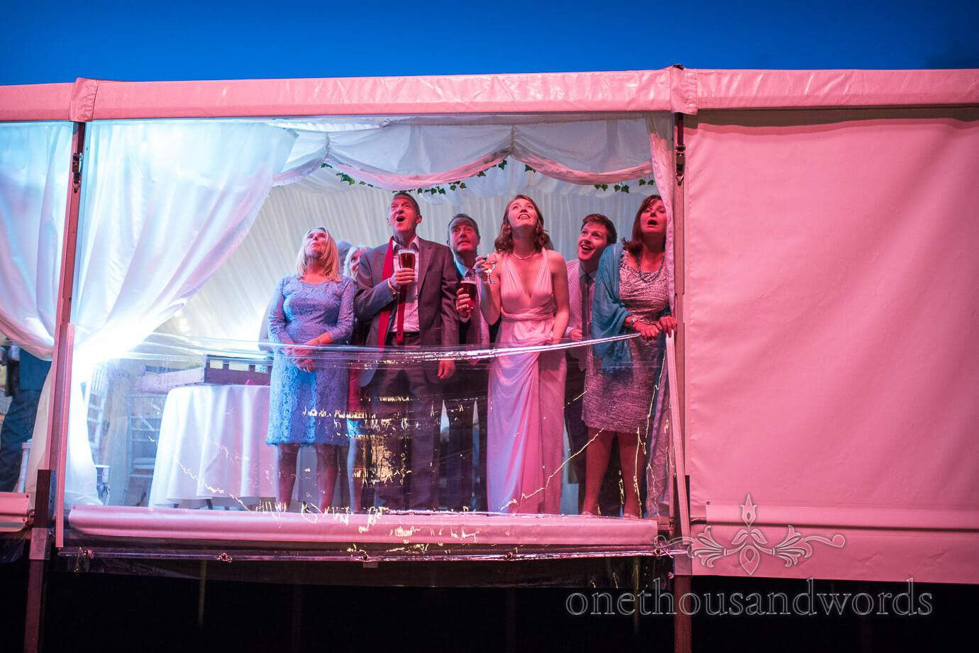 Wedding guests lit red watching wedding fireworks from marquee