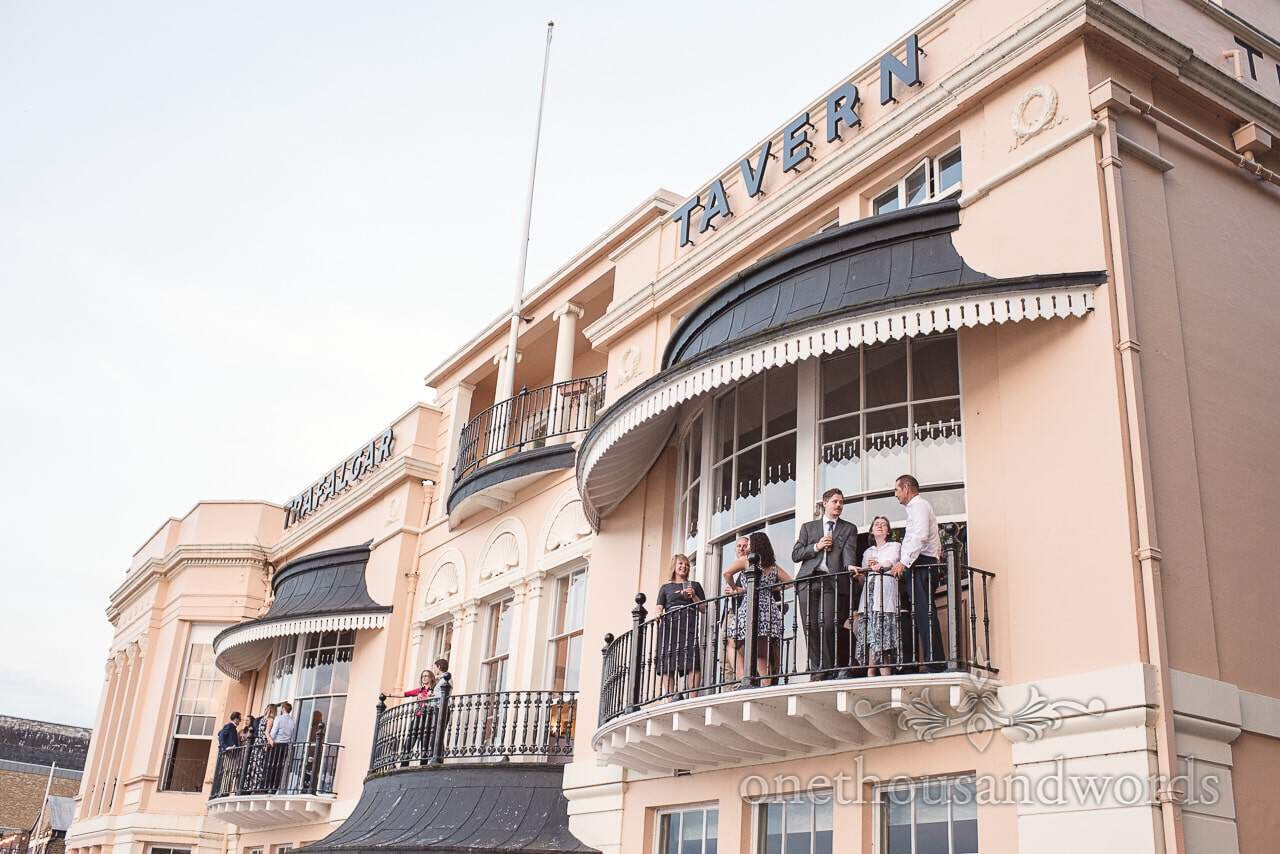 Wedding guests on ornate balconies at Trafalgar Tavern overlooking Thames