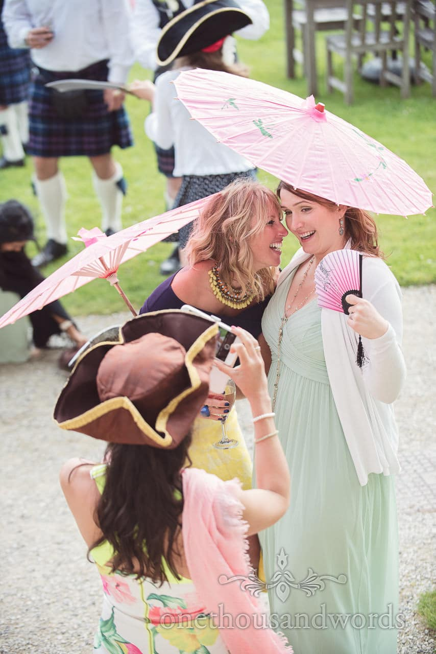 Wedding guests pose for photograph under pink parasols at pirate themed wedding
