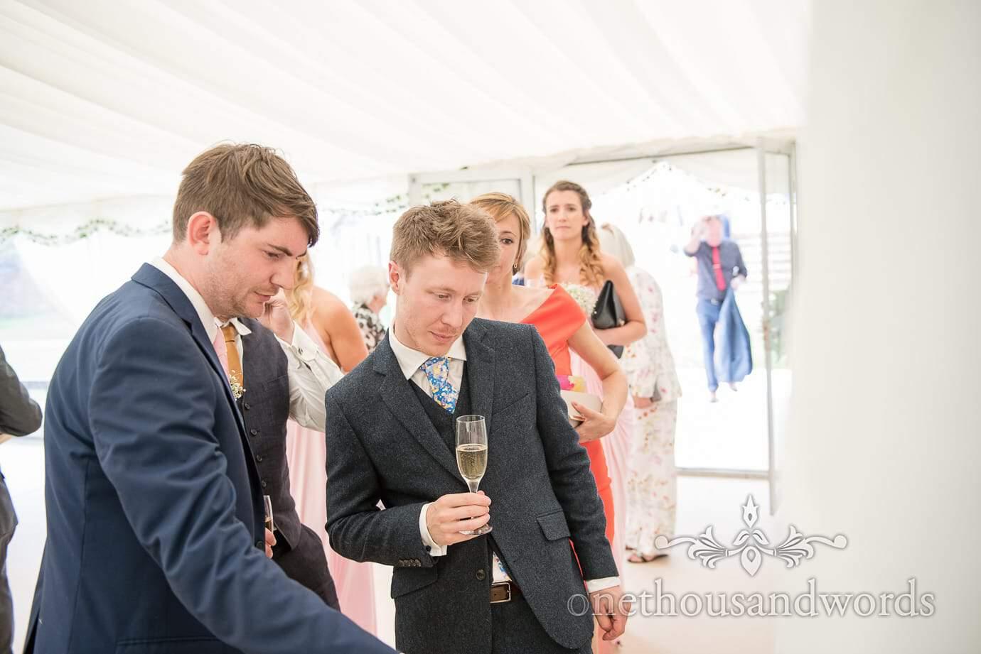 Wedding guests queue to examine table plan in wedding marquee