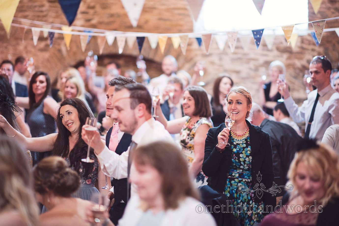 Wedding guests raise a toast during speeches at rustic barn wedding with bunting