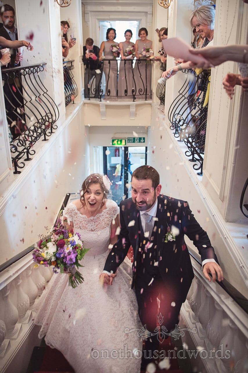 Wedding guests shower bride and groom with confetti from balcony at Trafalgar Tavern