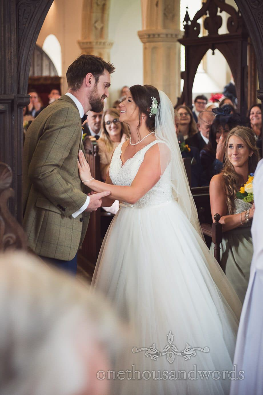 Wedding guests watch Bride and groom embrace during church wedding ceremony