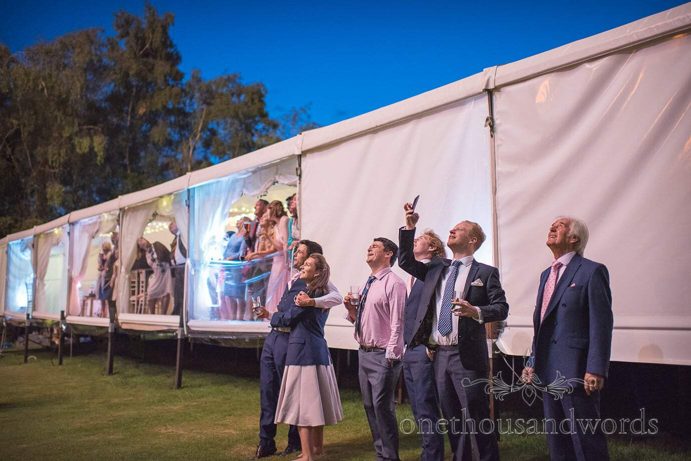 Wedding guests watch wedding fireworks in the night sky