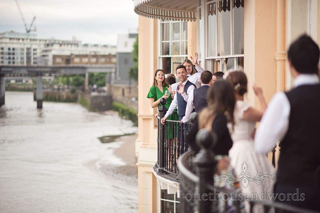 Wedding guests waving on Thames balcony at Trafalgar Tavern Wedding venue