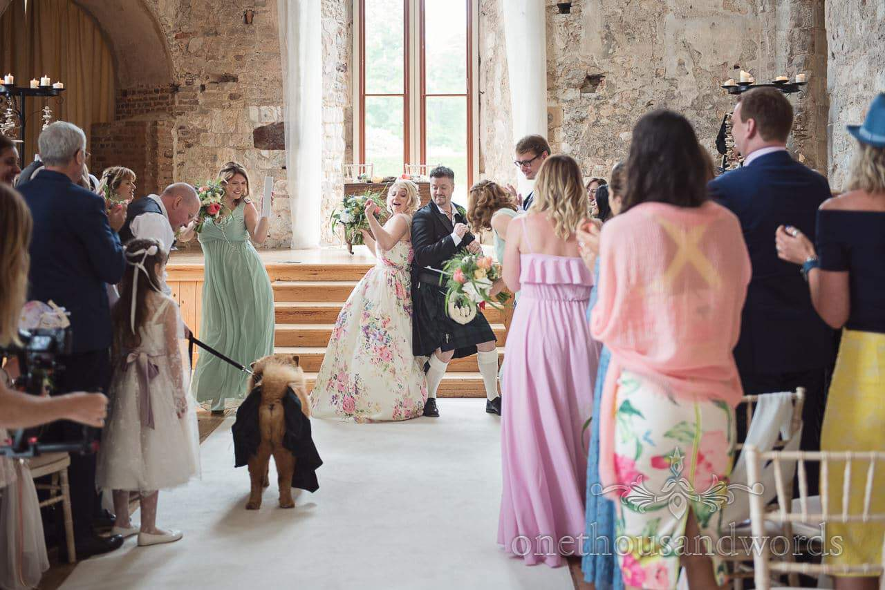Wedding party celebrate wedding ceremony with dancing at Lulworth Castle