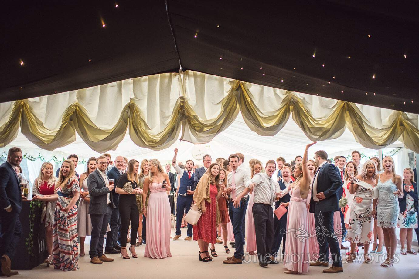 Wedding star cloth marquee dance floor is revealed to cheering wedding guests