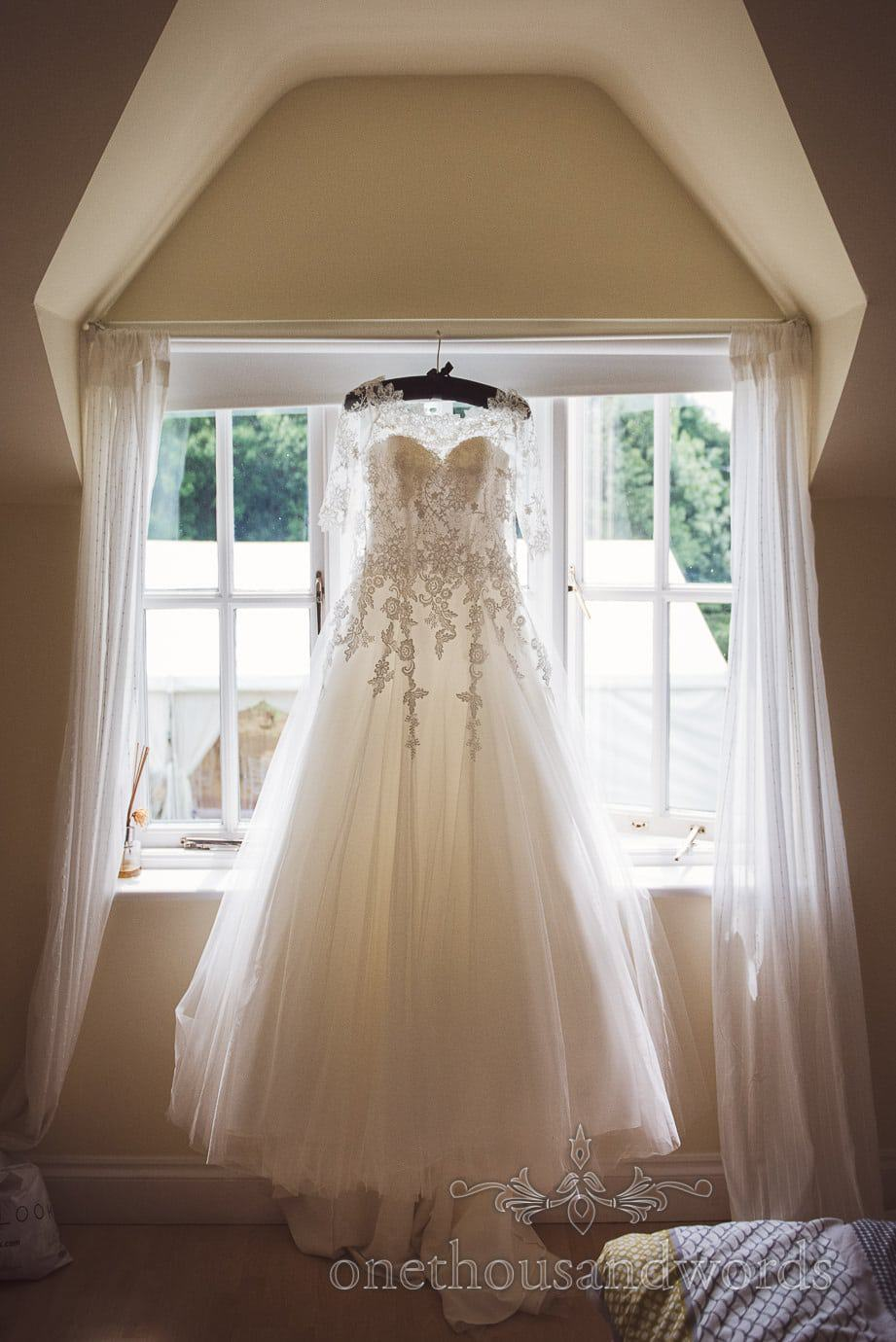 White A Line backless dress with lace detailing and lace bolero hang backlit in window