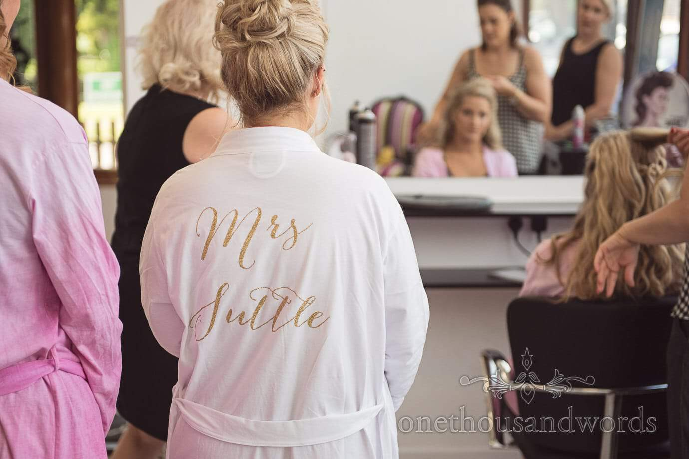 White bridal dressing gown with gold script name lettering in beauty salon on wedding morning