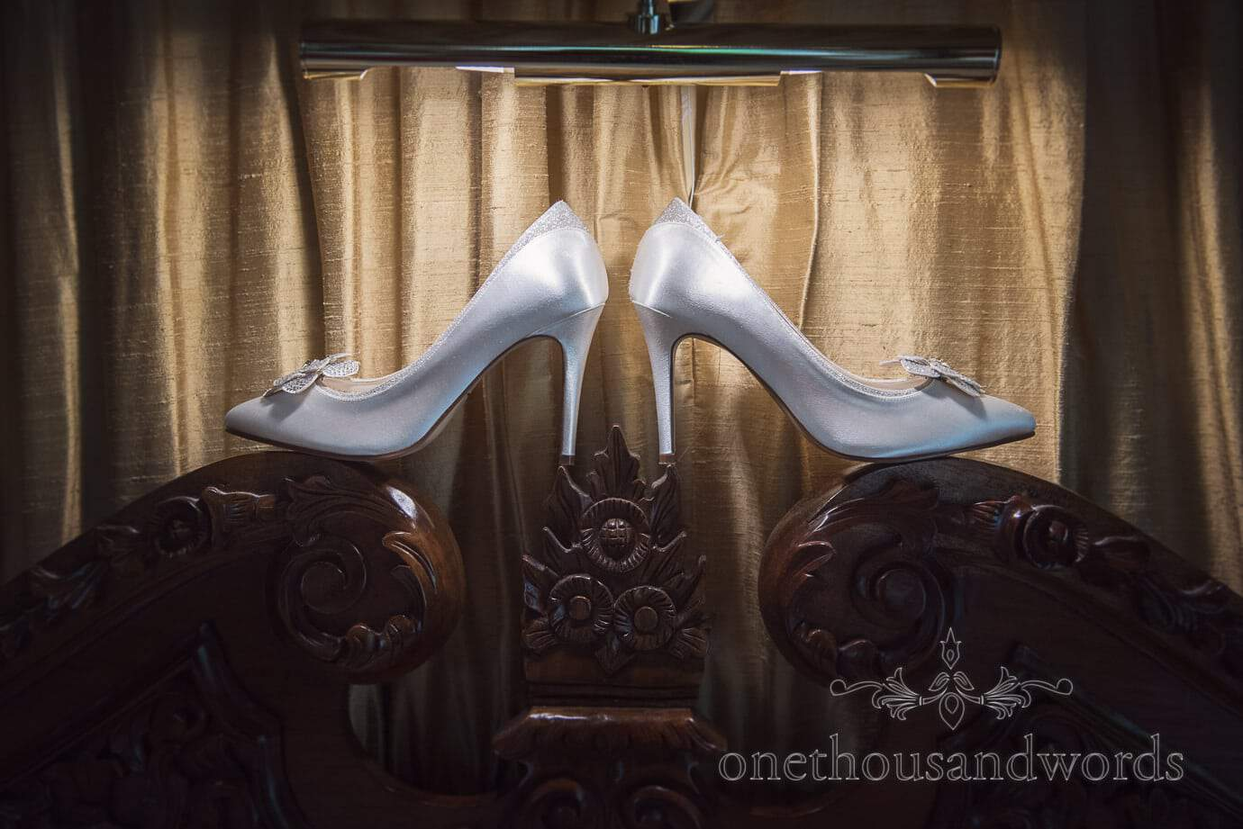 White satin wedding shoes with gold curtains on ornate wooden headboard under reading light