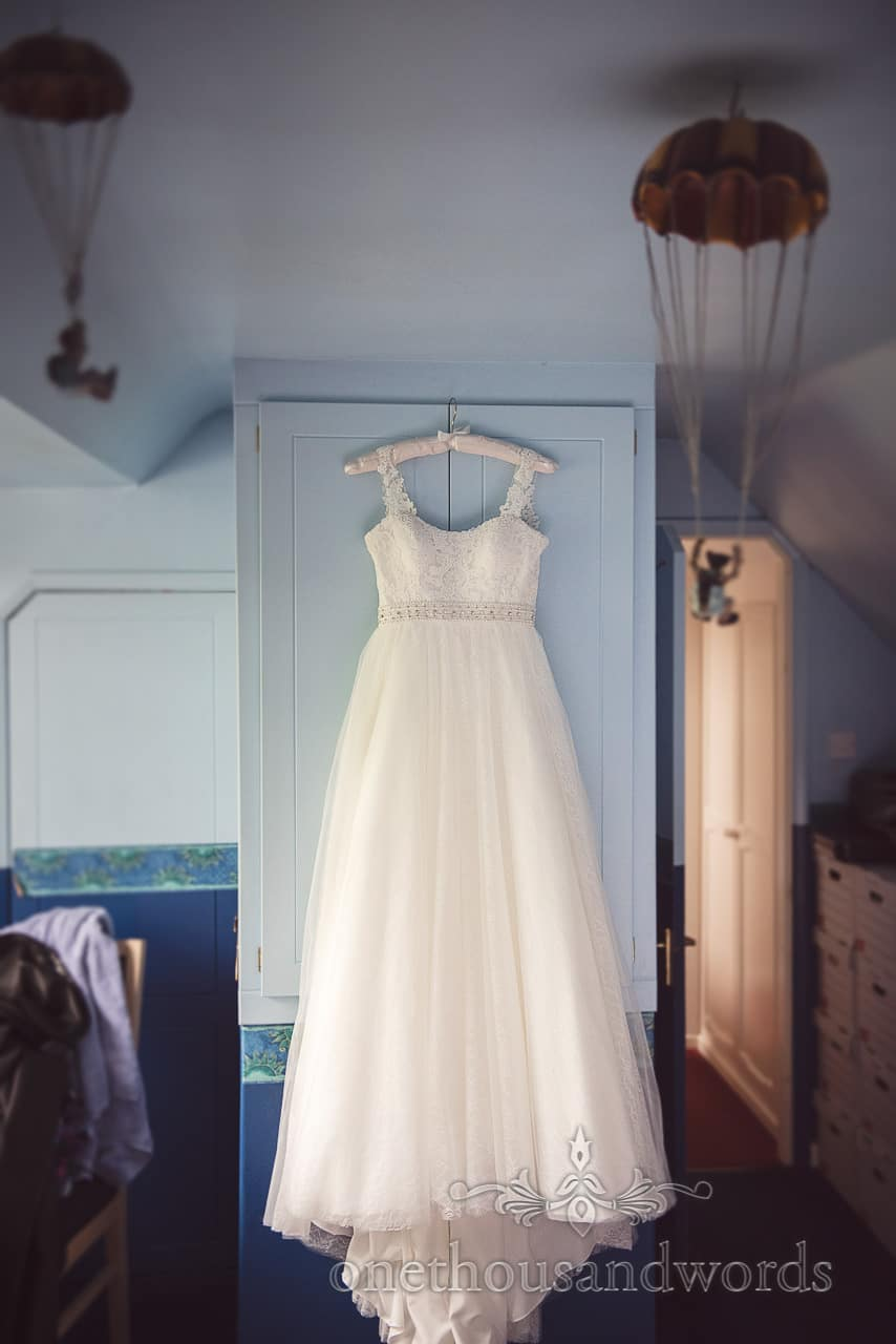 White wedding dress hangs on blue bedroom doors with parachute models