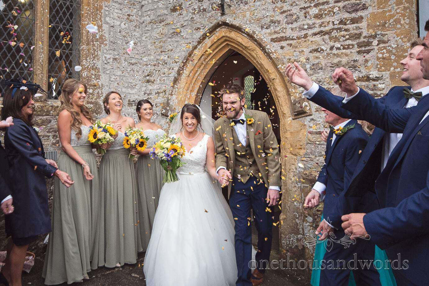 Yellow wedding confetti photograph outside Dorset stone church wedding
