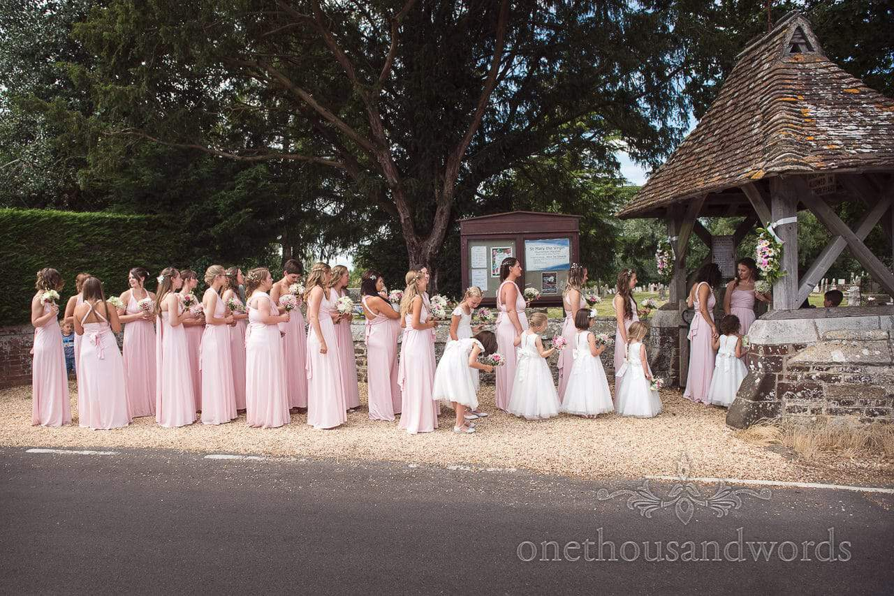 28 bridesmaids in pink bridesmaids dresses outside countryside church wedding venue