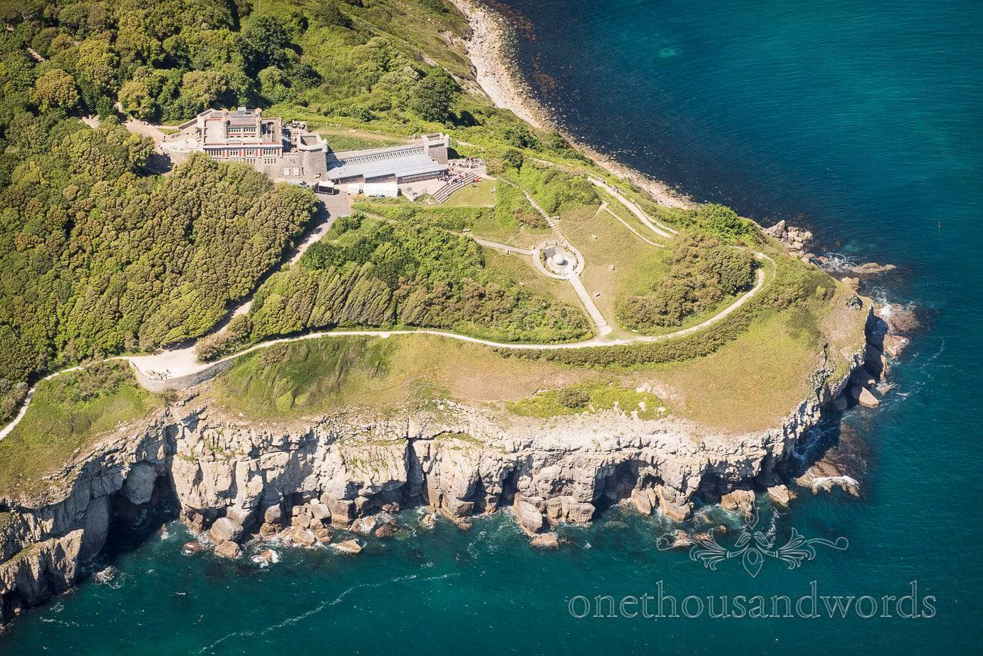 Aerial photograph of Durlston Castle wedding venue by the sea from wedding helicopter
