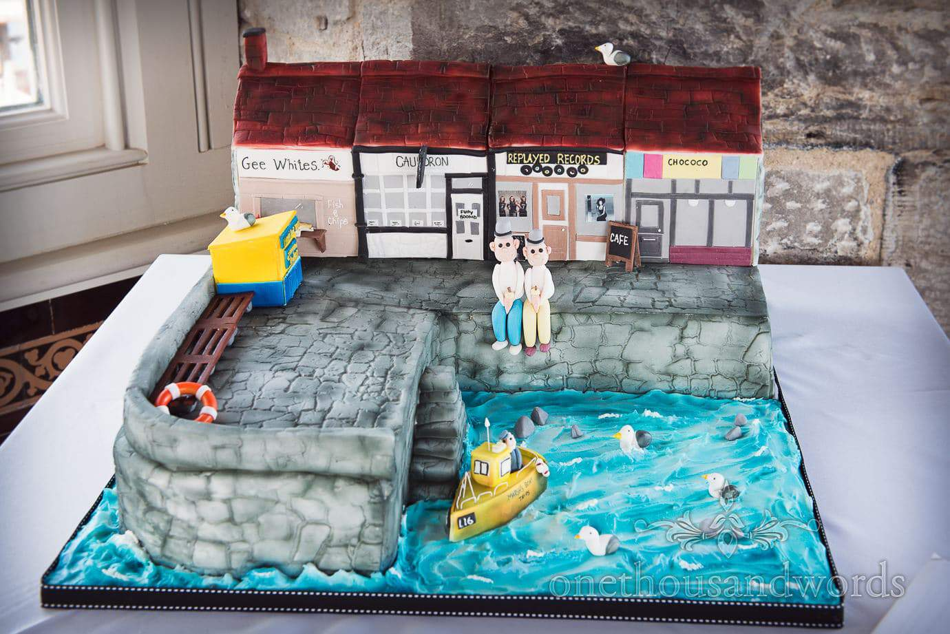 Amazing wedding cake with gay grooms in Swanage local scene by the seaside