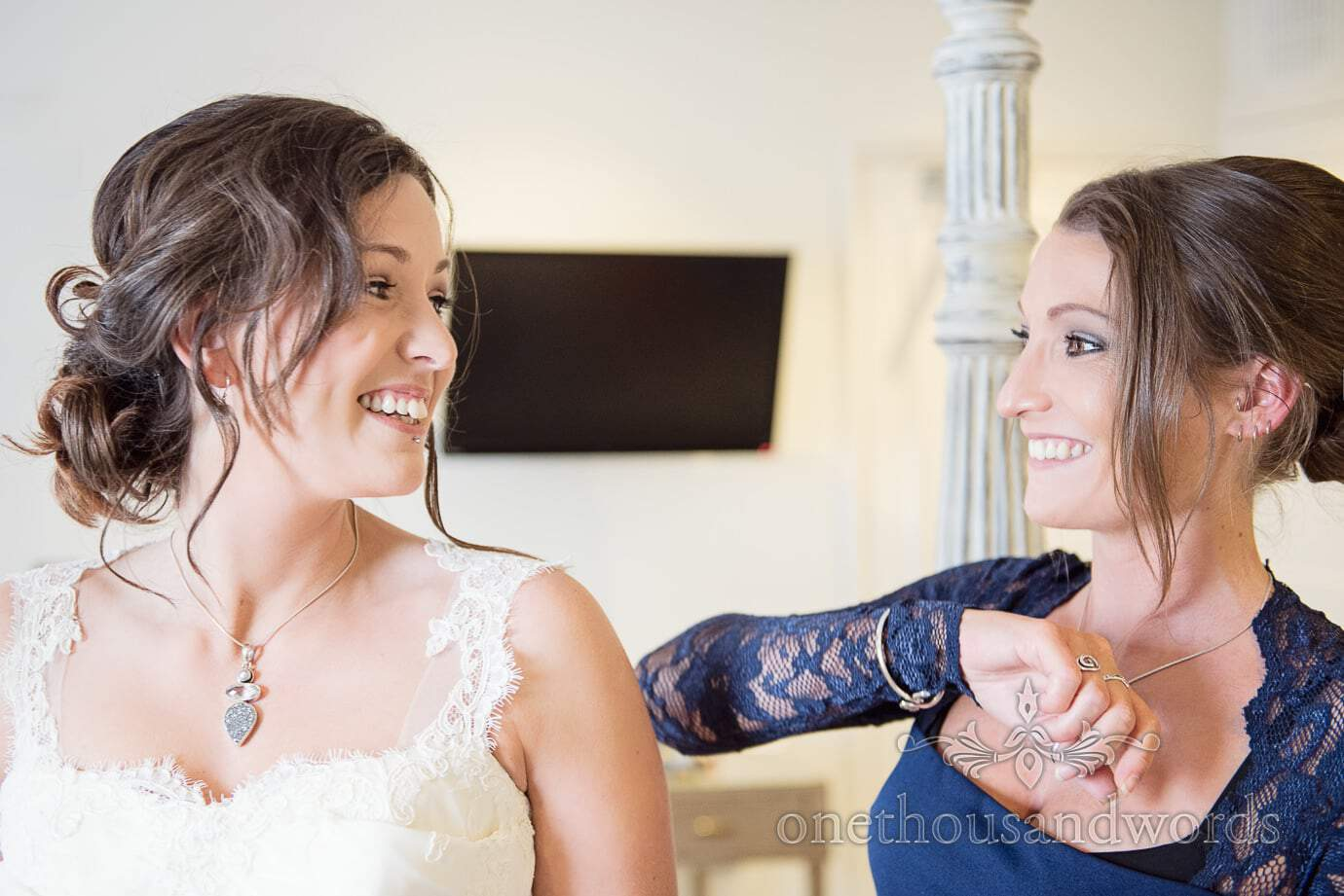 Beautiful brunette bride and bridesmaid look at each other during wedding preparations