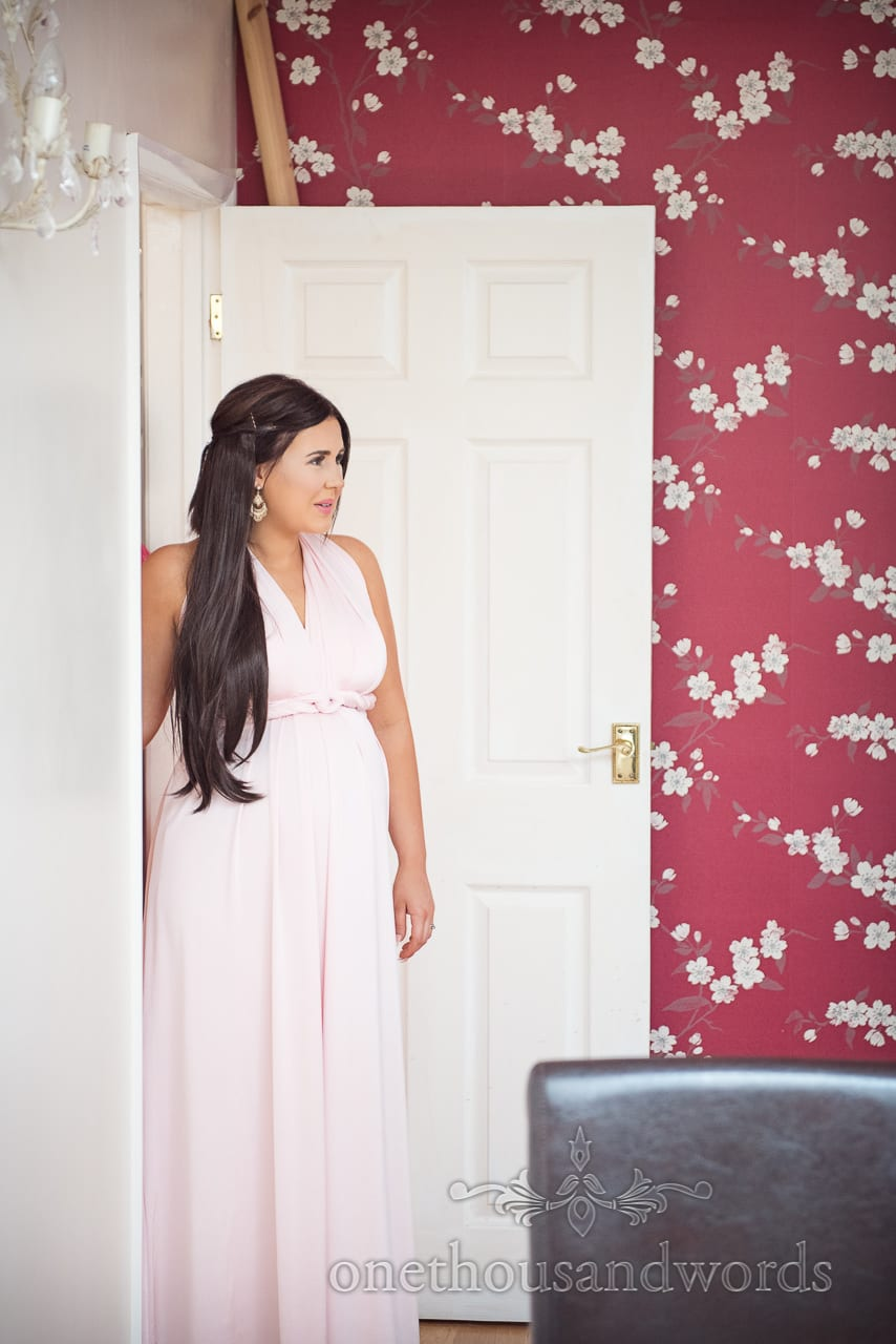 Beautiful pregnant bridesmaid in pink bridesmaid dress and red floral wallpaper