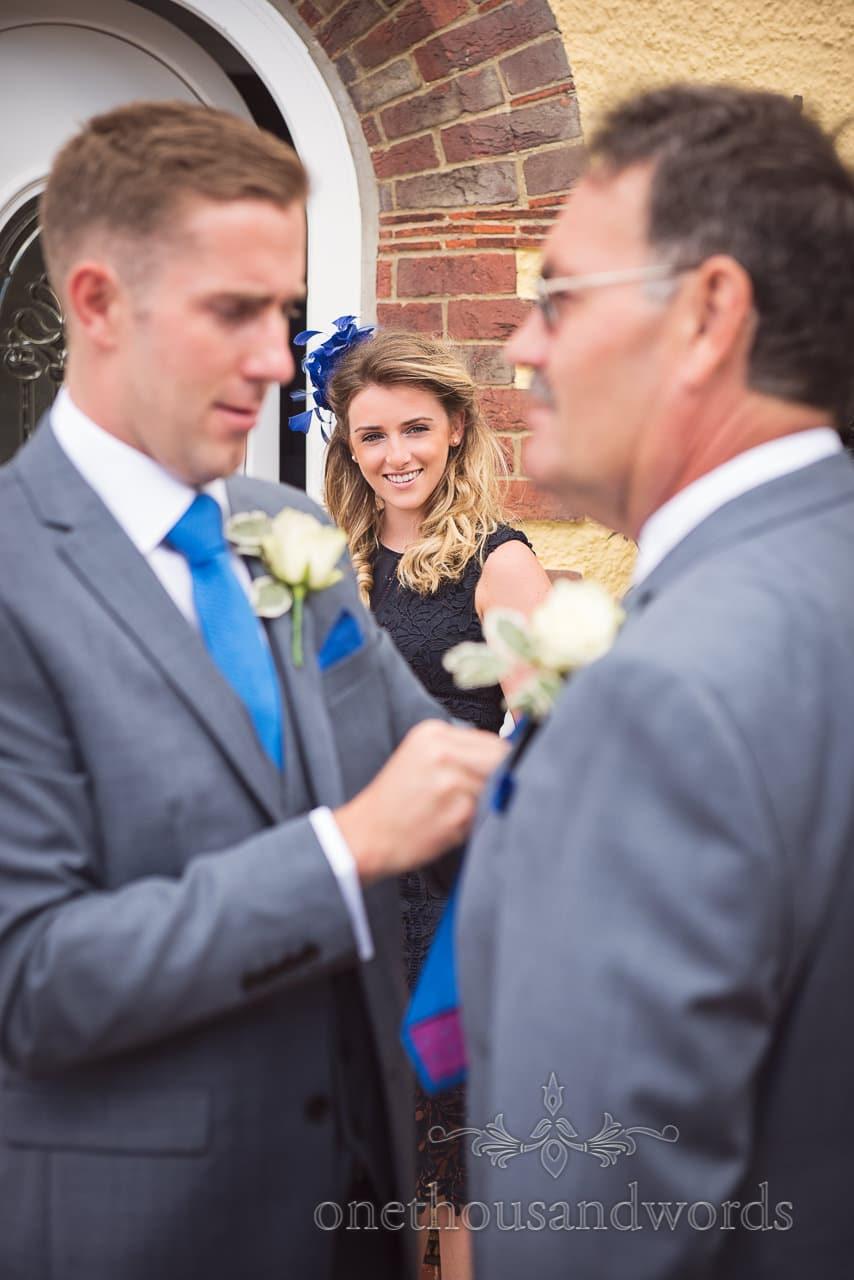 Beautiful wedding guest with blue fascinator watches groomsmen tying ties