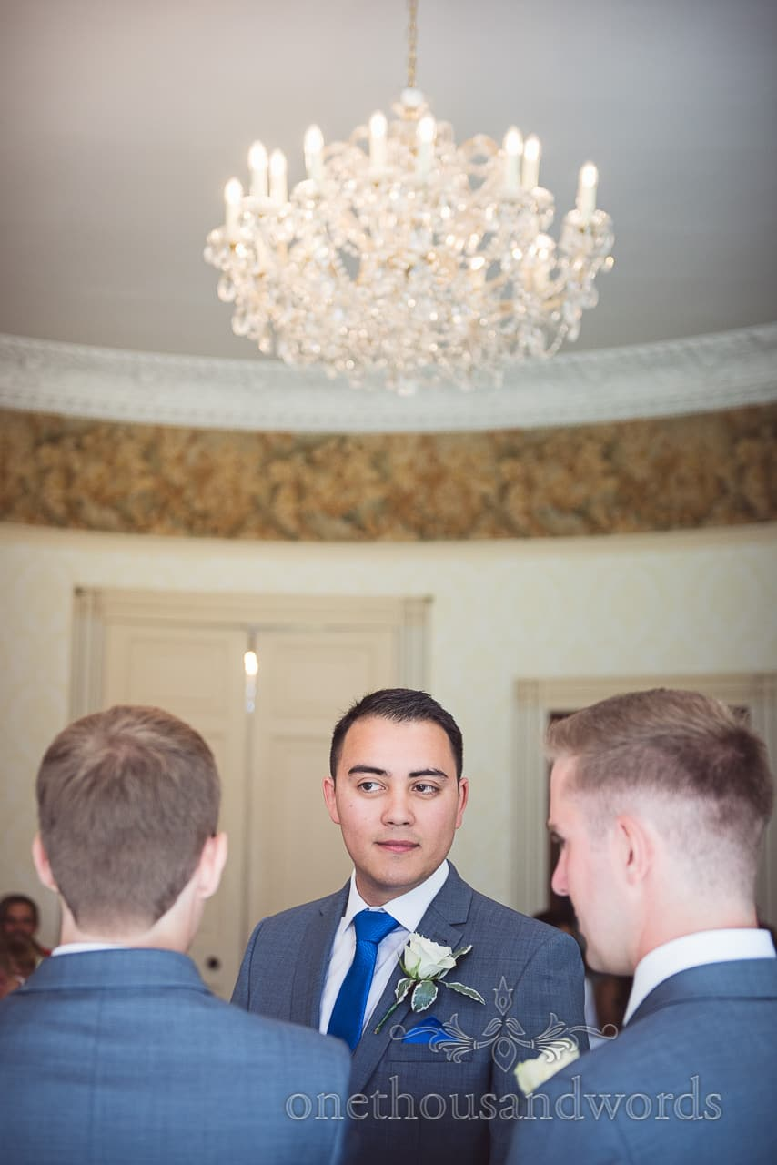 Best man in grey wedding suit with blue tie under huge chandelier at Upton House
