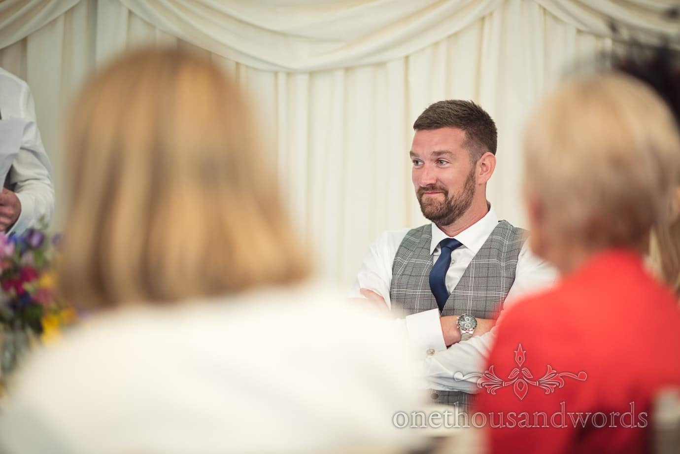 Best man in Prince of Wales check waistcoat and blue tie in wedding marquee