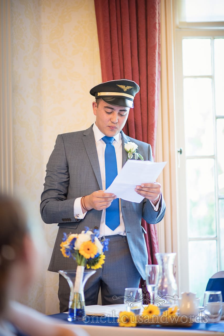 Best man's speech in plane captain's hat with grey suit and blue tie at Upton House