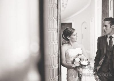 Black and white documentary wedding photograph of bride and groom at Upton House