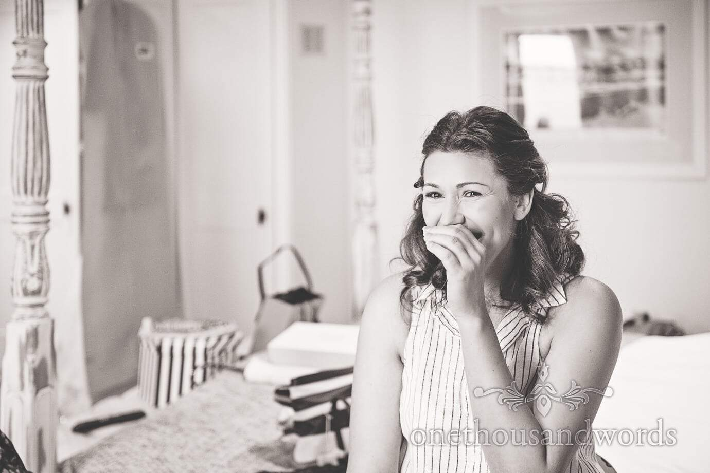 Black and white portrait photograph of bride laughing during wedding preparations
