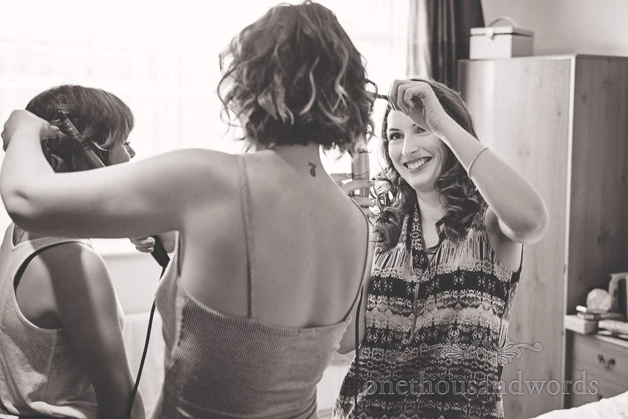 Black and white wedding photograph of bridesmaids styling each others hair