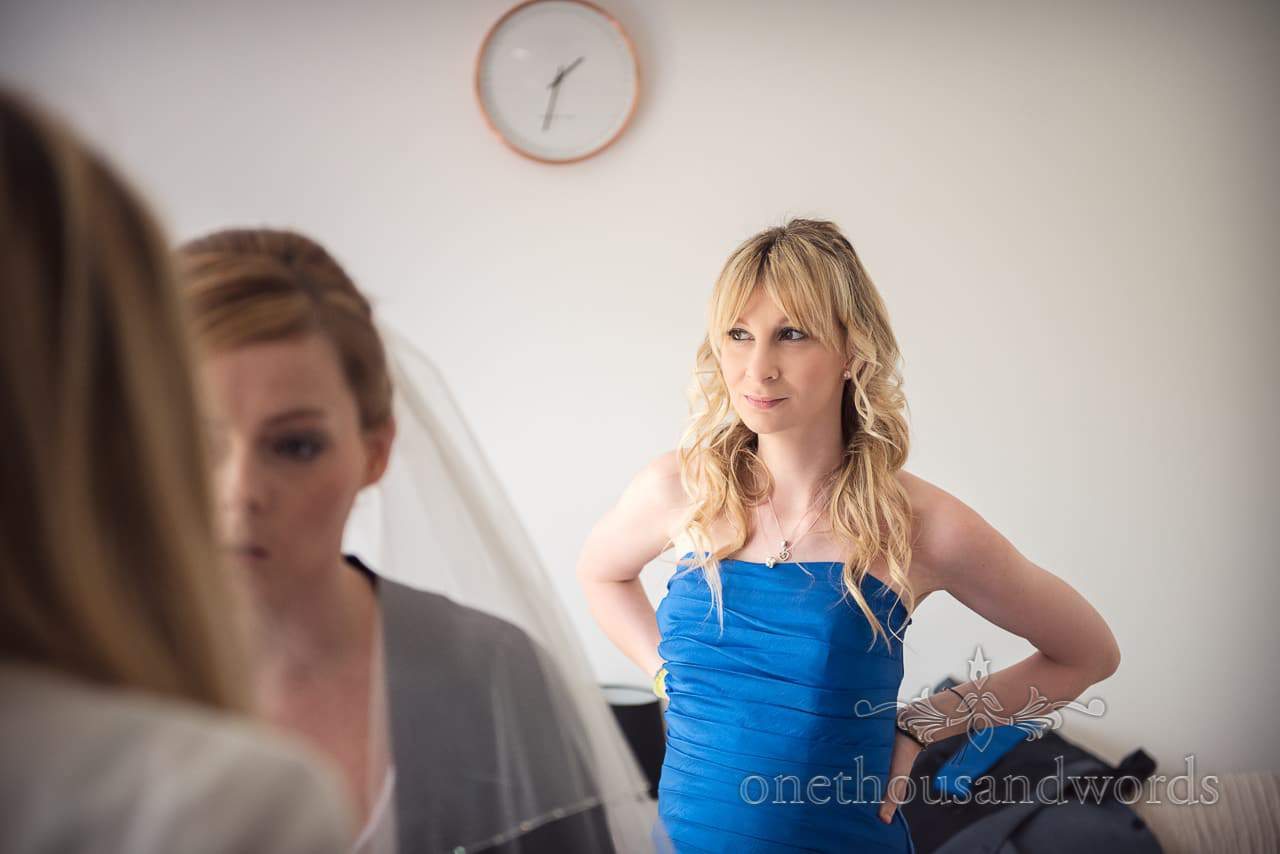 Blonde bridesmaid in blue bridesmaids dress watches wedding morning preparations