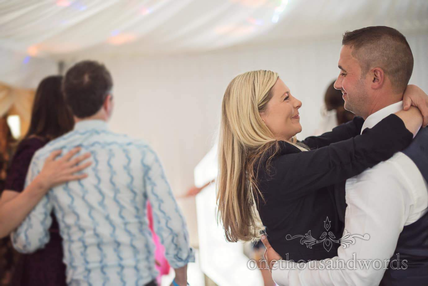 Blonde wedding guest dances with husband in marquee at The Old Vicarage Wedding