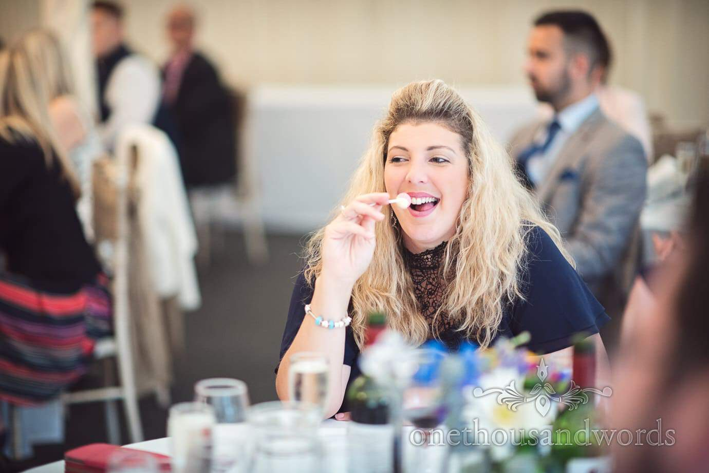 Blonde wedding guest enjoys lolly pop during wedding speeches at The Old Vicarage Wedding