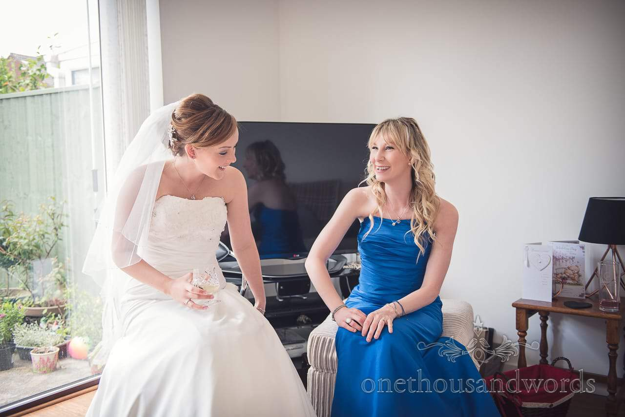 Bride and bridesmaid in blue dress laughing during wedding morning preparations