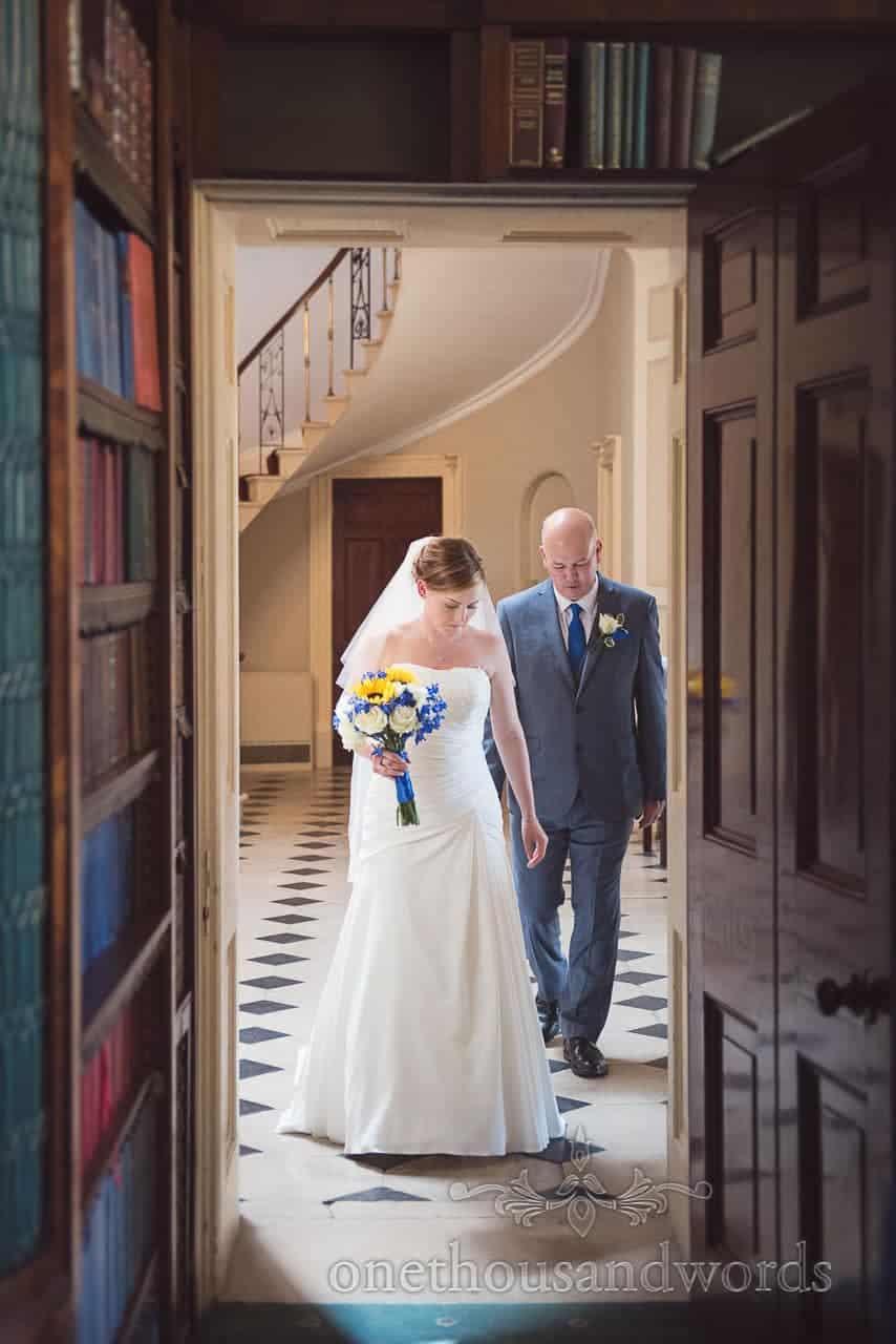 Bride and father enter Upton House wedding through bookcase