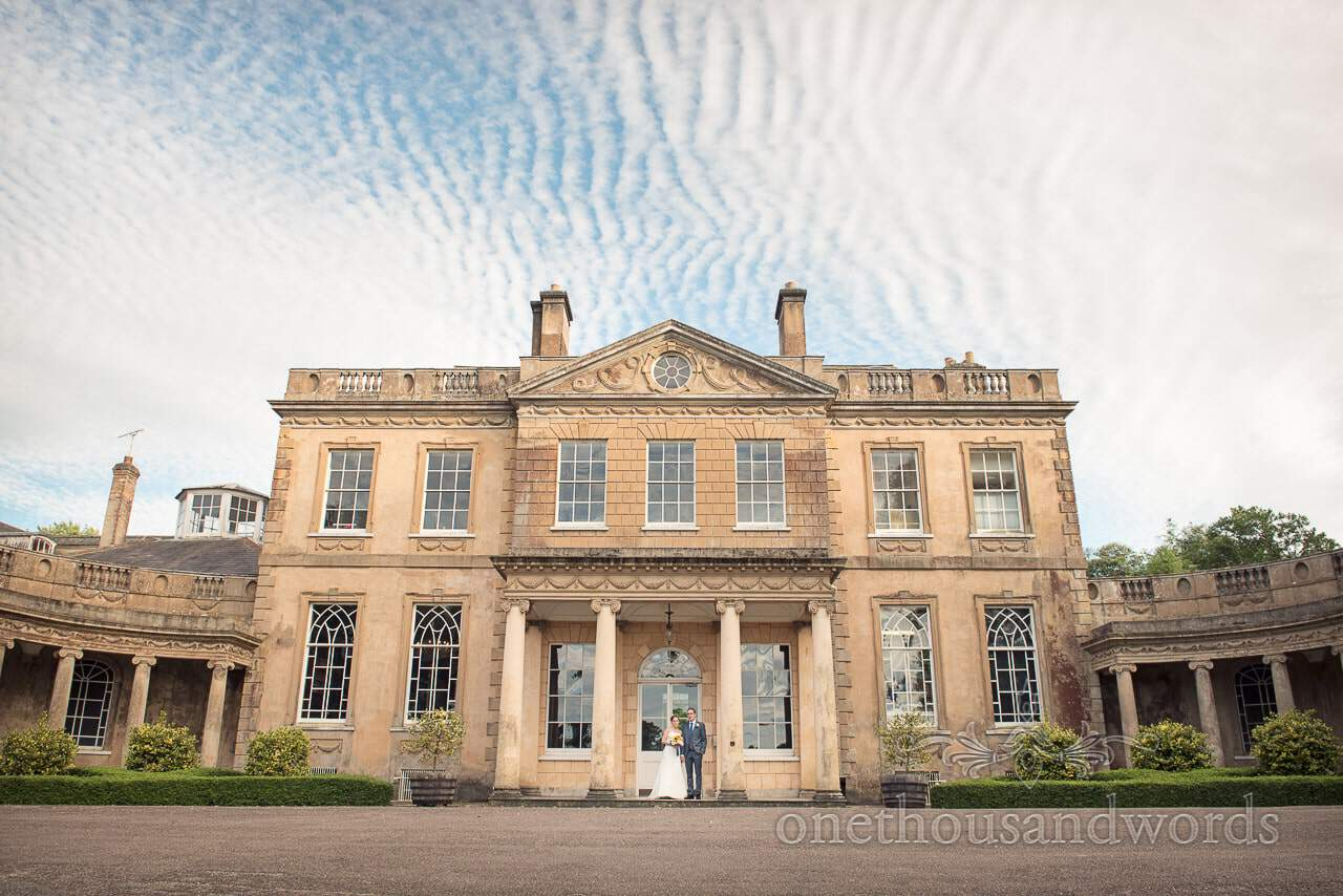 Bride and groom at Upton House stately home wedding venue in Dorset with rippled clouds