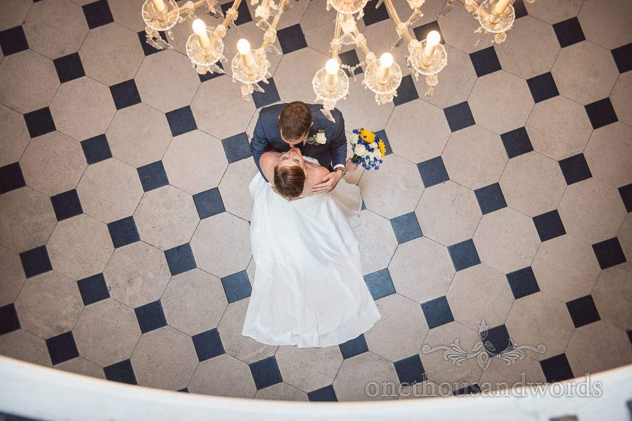 Bride and groom from above on black and white tiled floor with chandelier at Upton House