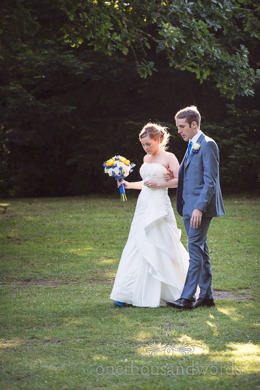 Bride and groom haloed by sunlight walk through woodland at Upton House wedding