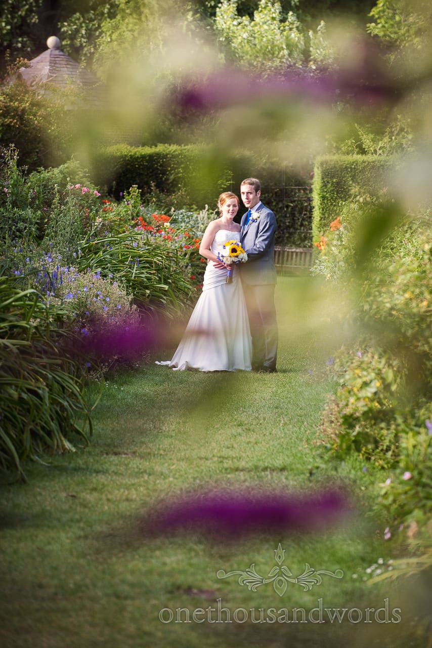 Bride and groom in flower gardens as Upton House wedding venue in Dorset