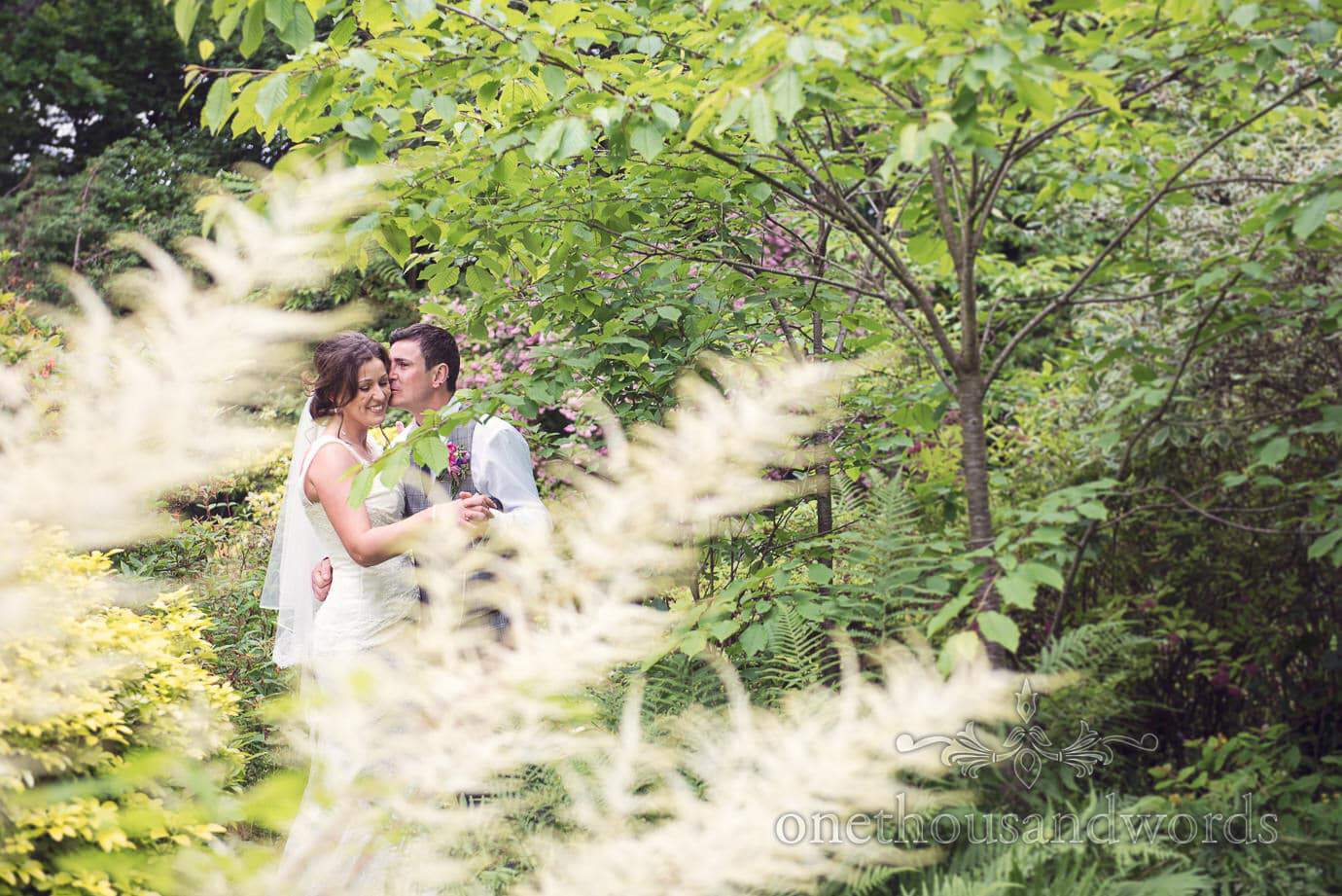 Bride and groom in green woodland gardens at The Old Vicarage Wedding venue