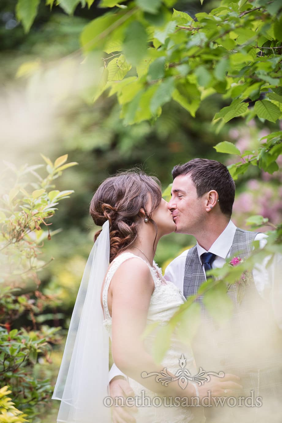 Bride and groom kiss in gardens at The Old Vicarage Wedding venue in New Forest