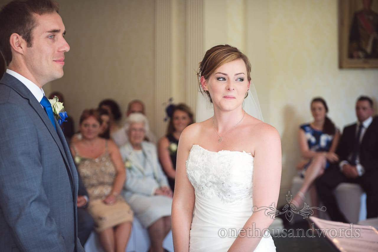 Bride and groom look at Registrar during civil wedding ceremony at Upton House