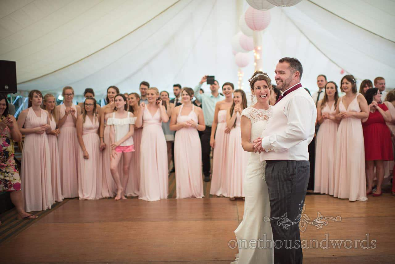 Bride and groom on marquee dance floor surrounded by bridesmaids in pink bridesmaids dresses