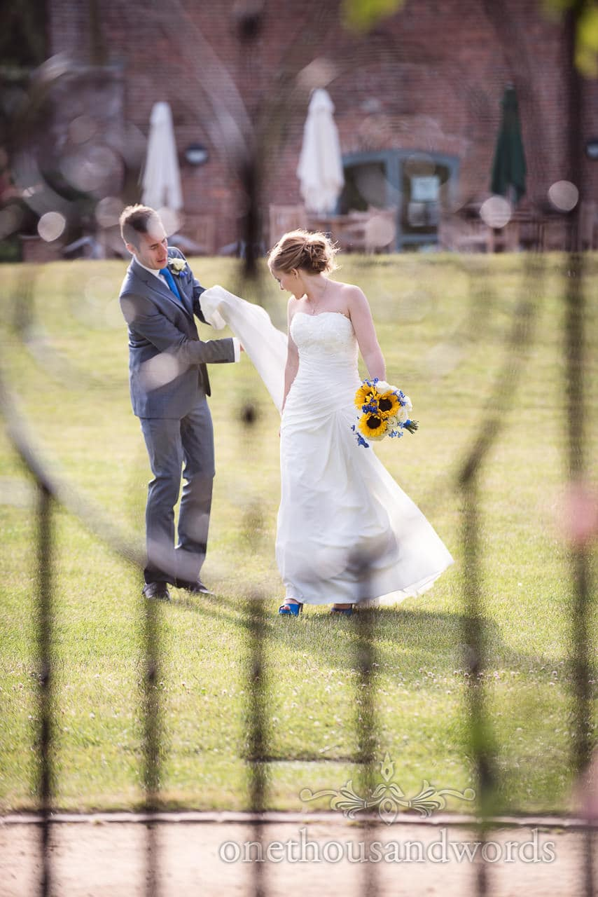 Bride and groom photographed through wrought iron gate at Upton House gardens