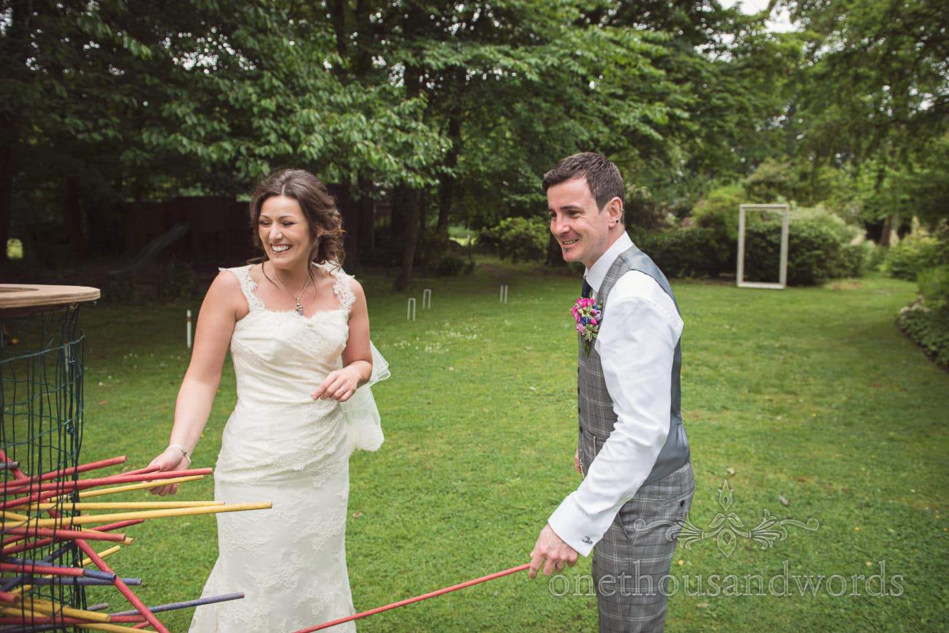 Bride and groom play giant kerplunk in The Old Vicarage Wedding venue gardens
